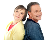 Portrait of senior couple back to back in studio Stock Images