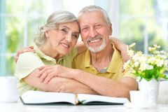 Portrait of senior couple with book drinking tea royalty free stock photos