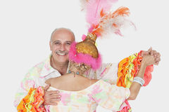 Portrait of senior couple in Brazilian outfits dancing over gray background Stock Photography