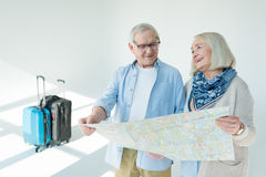 Portrait of senior couple choosing destination of trip on grey. Traveling concept Stock Images