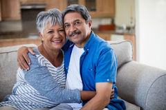 Portrait of senior couple embracing each other on sofa in living room Royalty Free Stock Image