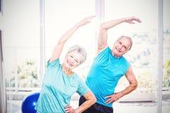 Portrait of senior couple exercising. Portrait of smiling senior couple exercising at home Stock Photography