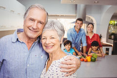 Portrait of senior couple with family preparing food in background Royalty Free Stock Photo