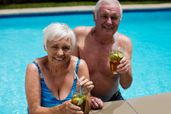 Portrait of senior couple holding glasses of iced tea. In pool Royalty Free Stock Photography