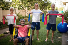 Portrait of senior couple holding multi colored ribbons. While exercising at park Royalty Free Stock Photos
