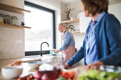 A portrait of senior couple indoors at home, cooking. A portrait of happy senior couple indoors at home, cooking stock photos