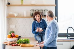 A portrait of senior couple indoors at home, talking. A portrait of happy senior couple with coffee indoors at home, talking stock photos
