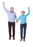 Portrait of senior couple jumping in joy stock photo