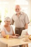 Portrait of senior couple with laptop. Woman typing on keyboard, looking at camera, smiling Royalty Free Stock Images