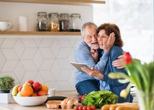 A portrait of senior couple in love indoors at home, using tablet. A portrait of happy senior couple in love indoors at home, looking for recipe using tablet royalty free stock images