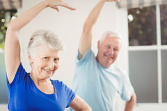 Portrait of senior couple performing stretching exercise Stock Images