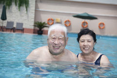 Portrait of senior couple relaxing in the pool Stock Image