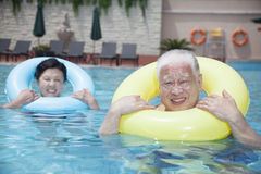 Portrait of senior couple relaxing in the pool with inflatable tubes Royalty Free Stock Image