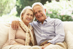 Portrait Of Senior Couple Relaxing On Sofa Stock Images