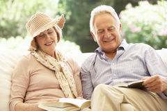Portrait Of Senior Couple Relaxing On Sofa Reading Together Stock Photos