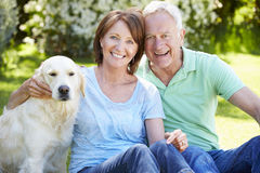 Portrait Of Senior Couple Sitting In Garden With Dog stock image