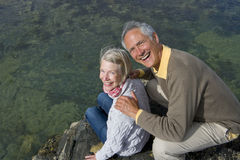 Portrait of senior couple sitting on rock, high angle view Stock Photo