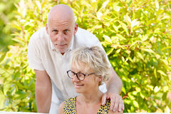 Portrait of a senior couple sitting on a sofa. Outdoors royalty free stock photography
