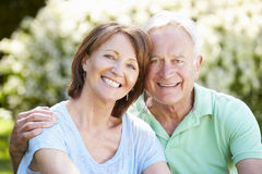 Portrait Of Senior Couple Sitting In Summer Garden Together royalty free stock image