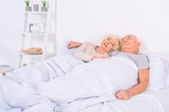 portrait of senior couple sleeping in bed together royalty free stock images