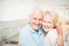 Portrait of senior couple smiling in kitchen Stock Images