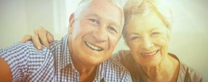 Portrait of senior couple smiling. In living room Stock Photo