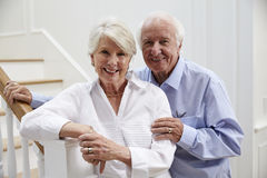 Portrait Of Senior Couple Standing By Staircase At Home Stock Photos