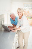 Portrait of senior couple using laptop in kitchen Royalty Free Stock Photos