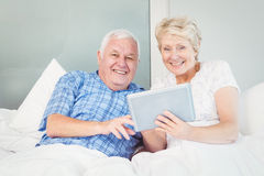 Portrait of senior couple using tablet on bed Stock Images