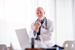 Portrait of a senior doctor in office. Stock Images