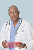 Portrait of a senior doctor holding clipboard over light blue background Royalty Free Stock Images