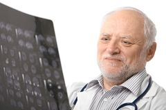 Portrait of senior doctor looking at X-ray image. Portrait of happy senior doctor looking at X-ray image, smiling. Isolated on white background Stock Image