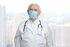 Portrait of senior doctor wearing medical protective mask. Old physician with stethoscope, bright city background Stock Image
