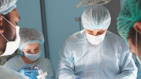 Senior surgeon performs the operation with a team of young assistants