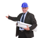 Portrait of a senior engineer presenting something and smiling. Isolated on white background Stock Photo