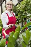 Portrait of a senior female gardener spraying pesticide on plants in botanical garden Stock Photo