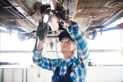 Portrait of a senior female mechanic in a garage. Female mechanic repairing a car. A senior woman working in a garage Stock Photos