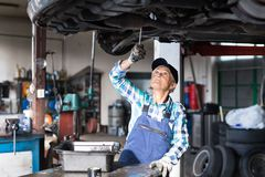 Portrait of a senior female mechanic in a garage. Female mechanic repairing a car. A senior woman working in a garage Royalty Free Stock Photography