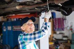 Portrait of a senior female mechanic in a garage. Female mechanic repairing a car. A senior woman working in a garage Stock Photo