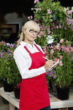 Portrait of a senior florist making notes in garden center Stock Photos