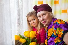 Portrait of senior grandmother with grandaugther with yellow tulips royalty free stock photography