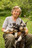 Portrait. Senior happy woman in glasses and two black and silver miniature schnauzer dogs in a garden Stock Image
