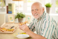 Portrait of senior having pizza. Portrait of senior man having pizza slice at home, smiling at camera Royalty Free Stock Images