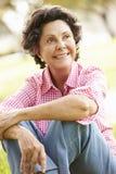 Portrait Of Senior Hispanic Woman Sitting In Park Stock Image