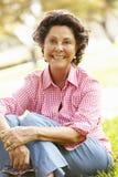 Portrait Of Senior Hispanic Woman Sitting In Park Royalty Free Stock Photo