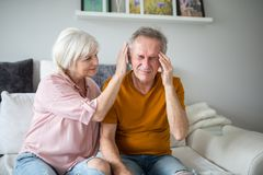 Senior lady comforting his husband with headache. Portrait of senior lady comforting his husband with headache Stock Images