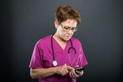 Portrait of senior lady doctor browsing on smartphone. On black background Stock Image