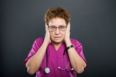 Portrait of senior lady doctor covering ears like deaf concept Stock Photography