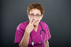 Portrait of senior lady doctor gesturing look into my eyes. On black background Royalty Free Stock Photos
