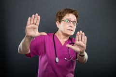 Portrait of senior lady doctor gesturing stop with both hands. On black background Royalty Free Stock Photos